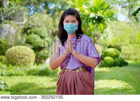 A Thai Woman In Traditional Thai Costume, Wearing A Surgical Mask, Is Show A Thai Greeting Call &quo