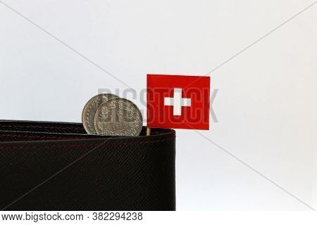 Two Coins Of One Swiss Franc And Mini Switzerland Flag Stick On The Black Wallet With White Backgrou