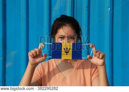 A Woman With Barbados Flag On Hygienic Mask In Her Hand And Lifted Up The Front Face On Blue Backgro