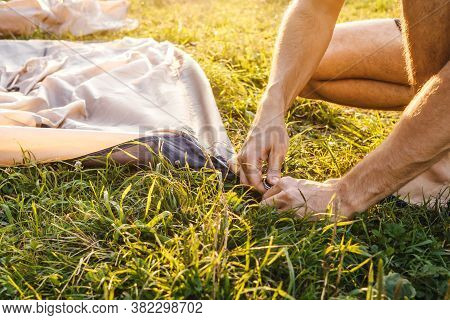 Close Up Of Male Hands Pegging Down Tent On Grass. Pitching Tent With A Stake. Sunset Light On Backg