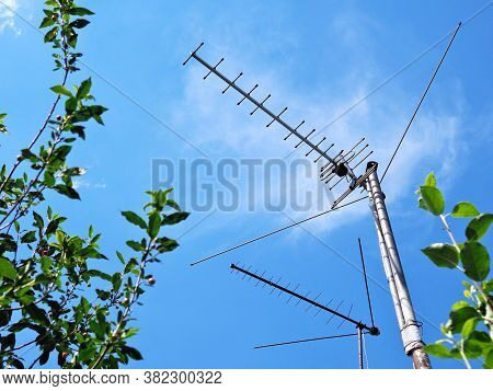Two External Tv Antennas Stand On Makeshift Poles Against The Blue Sky. Shot In The Summer In The Co