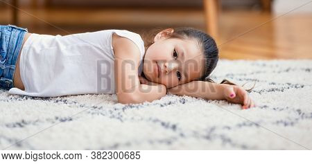Bored Chinese Little Girl Lying On Floor Looking At Camera At Home. Boredom Concept. Panorama