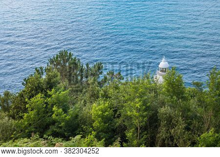 Lighthouse Behind The Trees In Cyan Sea.