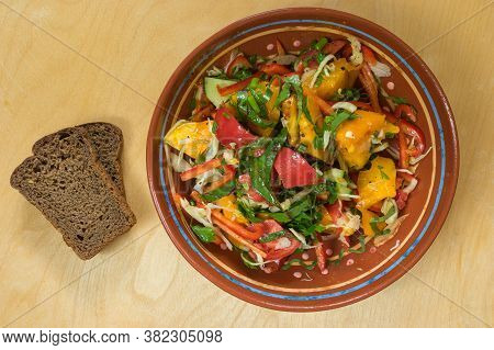 Top View On Ceramic Bowl Full Of Vegan Salad With Red Tomotoes, Cucumbers, Mangold , Parsley  Standi