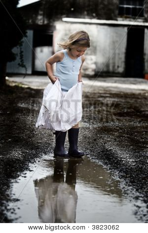 Young Girl In Dress And Wellies In Puddle