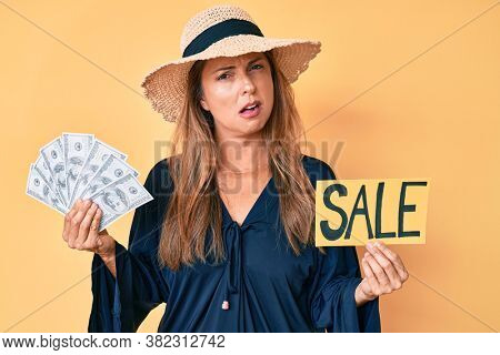 Middle age hispanic woman wearing summer hat holding sale banner and dollars in shock face, looking skeptical and sarcastic, surprised with open mouth