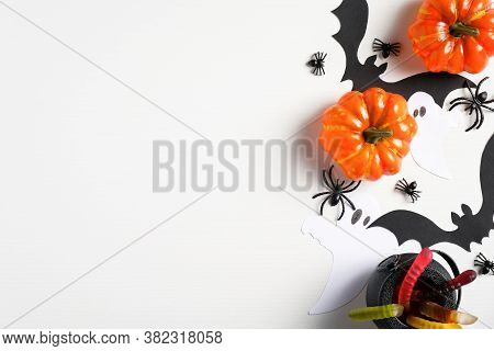 Halloween Flat Lay Composition With Pumpkins, Buts, Treats, Spiders On White Desk. Halloween Backgro
