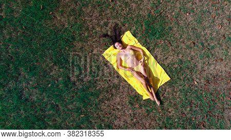 beautiful girl in bikini lying on a meadow