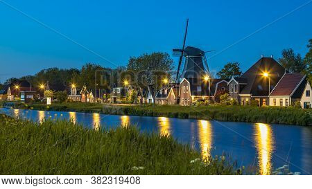 Typical Traditional Dutch Village With Farms And Windmill Along Canal In Twilight, Alkmaar, Noord Ho