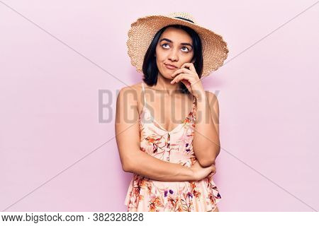 Young beautiful latin woman wearing summer hat thinking concentrated about doubt with finger on chin and looking up wondering
