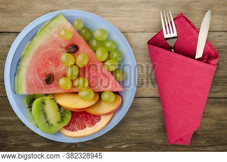 Sliced Fruit On A Wooden Background. Sliced Fruit On A Light Blue Plate Top View.sliced Fruig Wigh F