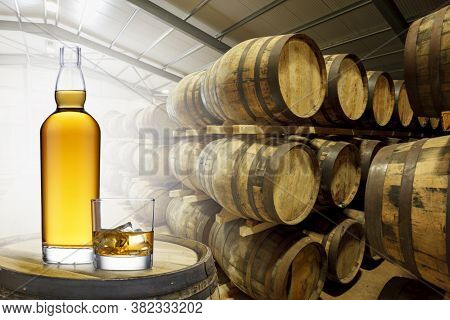 A Bottle And Glass Of Amber Whisky Set On Top Of An Old Barrel, In A Barrel Warehouse, Back Lit With