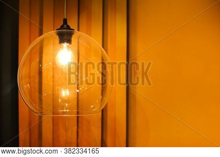 Low Angle Set Of Creative Transparent Glass Lamp With Glowing Bulb Hanging On Ceiling In Room With O