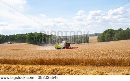 Two Modern Combines At Work In Field During Wheat Harvesting Season On Sunny Day. Harvesters Harvest