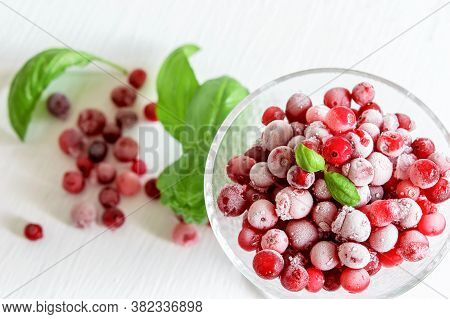Frozen Cranberries In Glass Bowl. Cranberries And Green Leaves Of Basil On The White Table. Top View