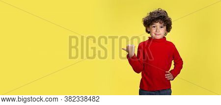 Pointing. Portrait Of Pretty Young Curly Boy In Red Wear On Yellow Studio Background. Childhood, Exp