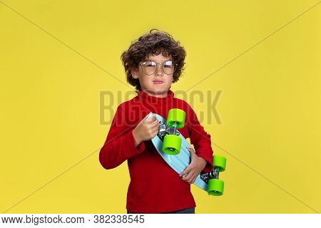 Skaterboy. Portrait Of Pretty Young Curly Boy In Red Wear On Yellow Studio Background. Childhood, Ex