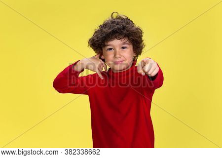 Need You To Call. Portrait Of Pretty Young Curly Boy In Red Wear On Yellow Studio Background. Childh