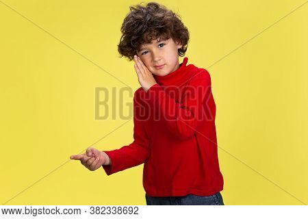 Gossip. Portrait Of Pretty Young Curly Boy In Red Wear On Yellow Studio Background. Childhood, Expre