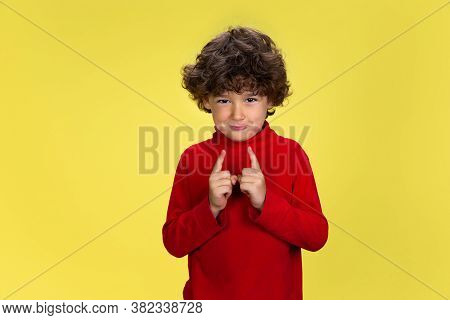 Showing Tiny. Portrait Of Pretty Young Curly Boy In Red Wear On Yellow Studio Background. Childhood,