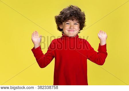 Happy, Smiling. Portrait Of Pretty Young Curly Boy In Red Wear On Yellow Studio Background. Childhoo