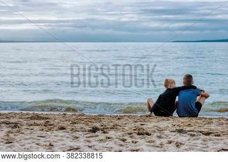 Two Young Brothers Sitting On A Beach. The Older Brother Is Looking At The Sea And An Island On The