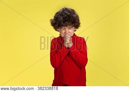 Praying. Portrait Of Pretty Young Curly Boy In Red Wear On Yellow Studio Background. Childhood, Expr