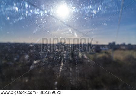 Blurred Image Of The Sun Through A Scratched Window Pane For Backgrounds