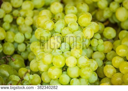 White Wine Grapes In A Market. The Grapes Are Green. Close Up Of A Large Cluster Of Green Grapes