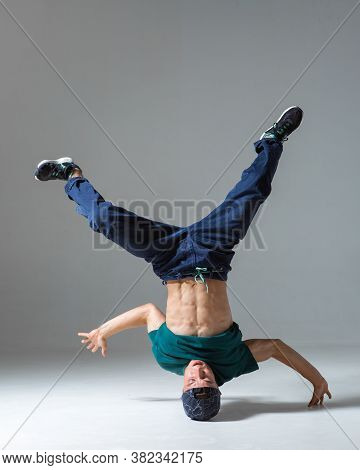 Stylish Guy Dancer Dancing On Head Breakdance In Studio Isolated On Gray Background. Breakdance Less