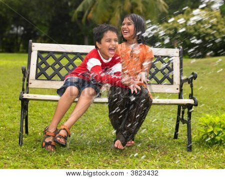 Asian Kids Playing In The Rain