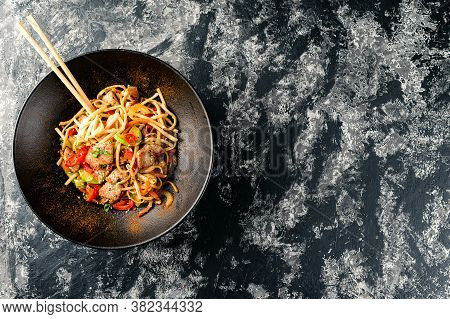 Udon Stir-fry Noodles With Chicken Meat In Bowl On Dark Stone Background Copy Space, Wok Noodles