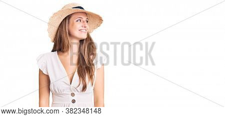 Young beautiful blonde woman wearing summer dress and hat looking away to side with smile on face, natural expression. laughing confident.