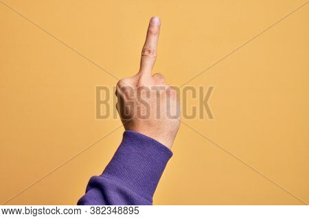 Hand of caucasian young man showing fingers over isolated yellow background showing provocative and rude gesture  symbol with middle finger