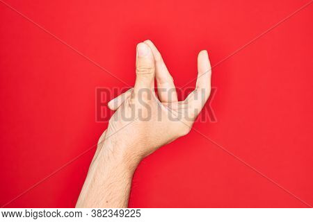 Hand of caucasian young man showing fingers over isolated red background snapping fingers for success, easy and click symbol gesture with hand