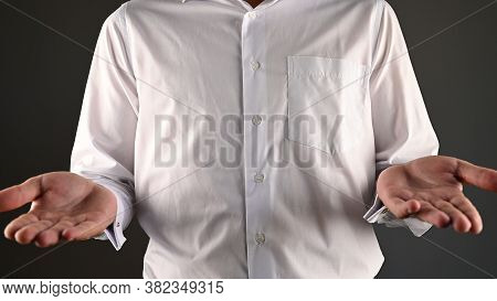 A Man In A White Shirt Makes A Helpless Gesture