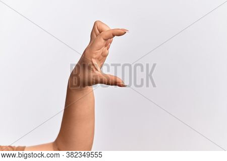 Hand of caucasian young woman picking and taking invisible thing, holding object with fingers showing space
