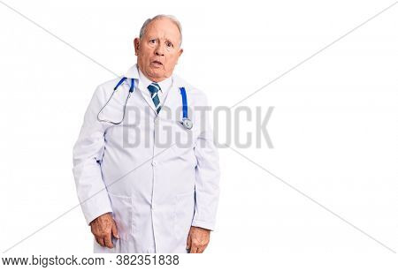 Senior handsome grey-haired man wearing doctor coat and stethoscope in shock face, looking skeptical and sarcastic, surprised with open mouth