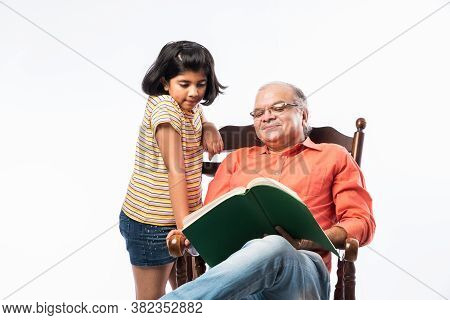 Indian Senior Man Or Grandpa Reading Book With Granddaughter Or Grand Daughter While Sitting On Rock