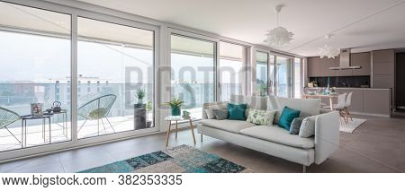 Modern living room with designer furniture. Sofa with light cushions and balcony view. Behind the modern kitchen with island. Nobody inside.