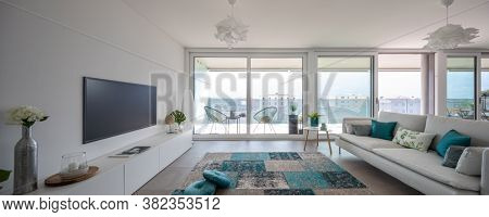 Modern living room with designer furniture. Sofa with light cushions and balcony view. Nobody inside. Frontal view, panorama