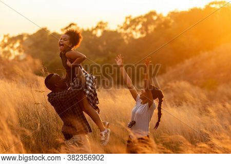 Happy African Family Father Mother And Child Daughter Travel And Running On Meadow Nature On Silhoue