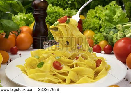 Plate Of Italian Pasta, Fettuccine On Fork With Tomatoes And Basil