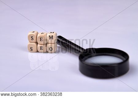 Sem And Seo Concept. Wooden Cubes With Seo And Sem Abbreviation. Toy Blocks With Letters And Magnifi