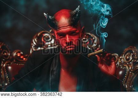 A close-up portrait of a bad demon with a cigar. Horror movie, nightmare. Halloween.