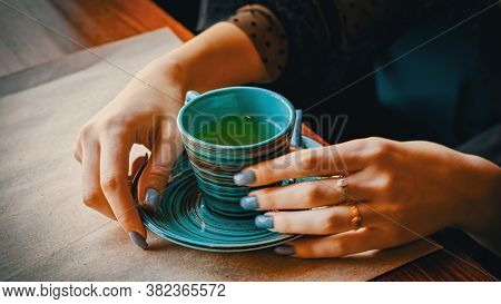The Girls Hands Touch The Cup Of Herbal Tea Standing In Front Of Her.