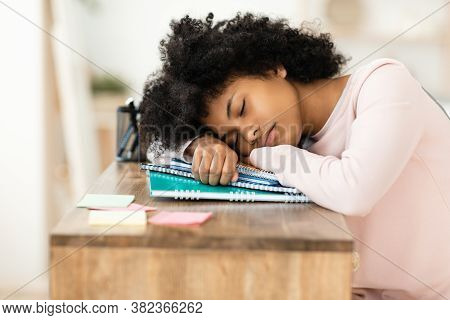 Overworked Black Teen Girl Sleeping During Class Resting Head On Books Indoors. Burnout In School