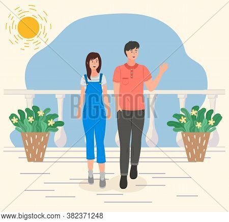 Couple Walking On The Sun White Terrace With Potted Plants. Smiling Young Guy And Girl On Holidays M