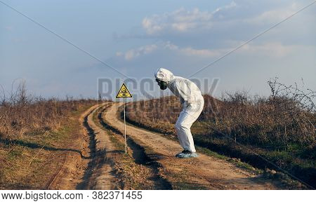 Side View Of Scientist In Suit And Gas Mask Standing By Yellow Triangle With Biohazard Symbol On The