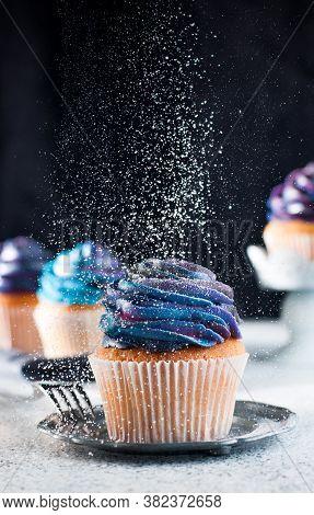 Vanilla Cupcake Sprinkled With Sugar Powder On Black Background